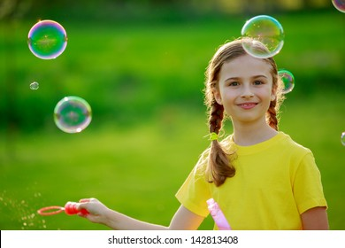 Children's games -  young girl playing with soap bubbles, happy childhood