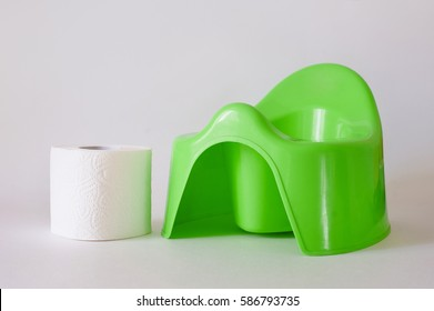 children's green pot and toilet paper on a white background