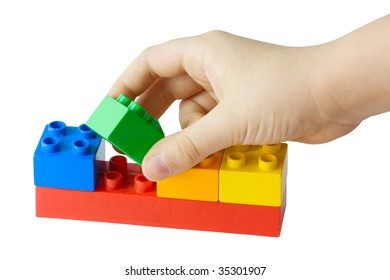 Children's hand collects toy cubes