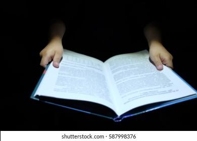 Children's hand holding a book on a dark background