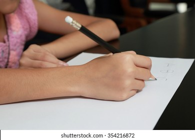 """children's hand holding the pencil writing """"A B C"""" text on white paper"""