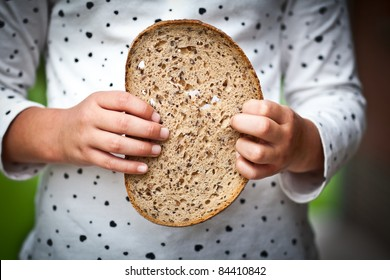 childrens hand holding a slice of bread