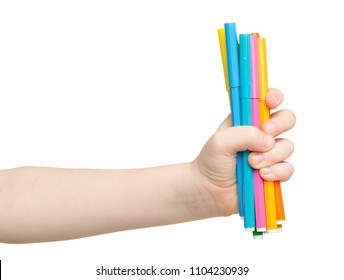 Children's hand holding stack of colorful markers isolated on white background. Art, creativity, education concept