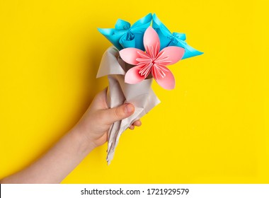 Children`s hand holds a bouquet of paper flowers made using the origami technique on a yellow background. DIY concept. Children's creativity. A gift for mother's day or women's day.