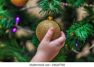 Children's hand holds a Christmas ball hanging on a Christmas tree Close up