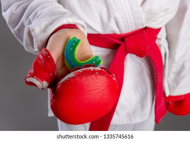 Children's hand in a red sports glove holds a protective cap for martial arts