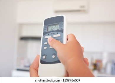 children's hand turns on the air conditioner using the remote control