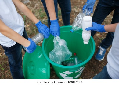 Children's hands in blue latex gloves holding plastic bottles on a park ground background. Ecology protection concept.