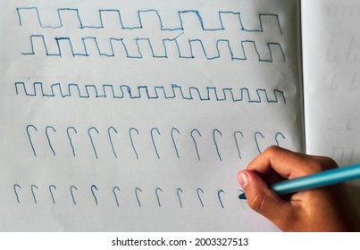 Children's hands with a blue pen on the table with a sheet of paper writes squiggles. View from above.