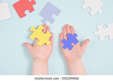 childrens hands colored hold puzzles on blue background, autism symbol, autism diagnosis concept