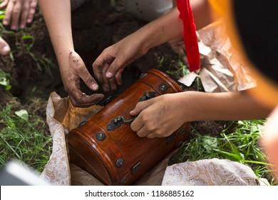 Children's Hands Dig Up the Earth in Treasure Hunt
