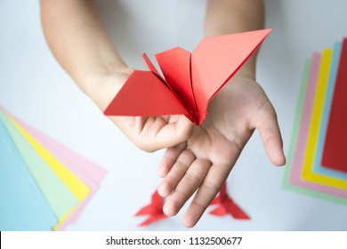 Children's hands do origami butterfly from colored paper on white background. lesson of origami butterfly.
