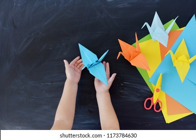 Children's hands do origami from colored paper. Lesson of origami. Color paper cranes on a black background. Creativity. The kid's hands