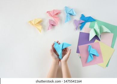 Children's hands do origami from colored paper on white background. lesson of origami. Flat lay