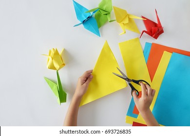 Children's hands do origami from colored paper on white background