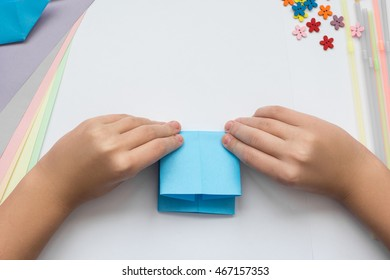 children's hands do origami on a table. Nearby sheets of color paper lie.