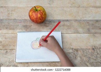 Children's hands draw an apple with colored pencils. Top view