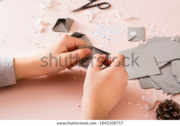 Children's hands fold envelopes for making an advent calendar on a table in Christmas decorations