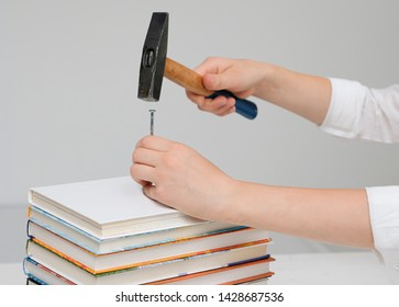 Children's hands hammer a nail into a pile of books; concept of reluctance to learn; neutral background