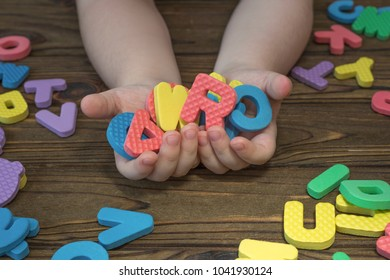 children's hands hold colored letters alphabet, abc. on a wooden background. Game, training, school.