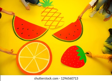 children's hands hold fruit from paper on a yellow backgroun.  healthy food. Concept summer lifestyle. Children's creativity.