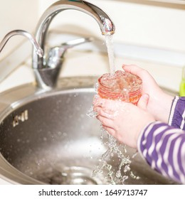 Children's hands hold a glass above the sink under a strong stream of water from the faucet.
