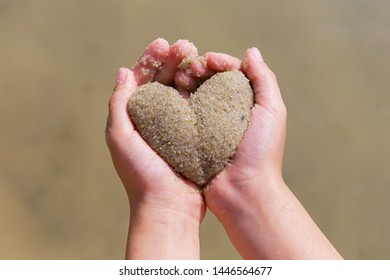 children's hands hold the heart out of the sand, summer, love concept
