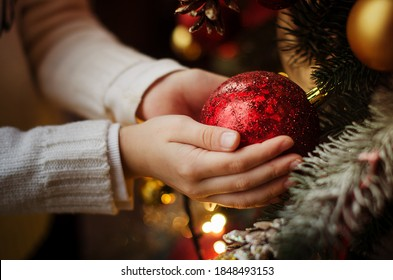children's hands hold a red shiny Christmas ball hanging on the Christmas tree.The tree is decorated with toys, garlands and lights. Christmas and new year family celebration concept