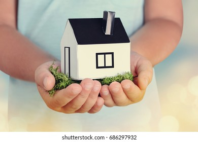 Children's hands hold small paper house.