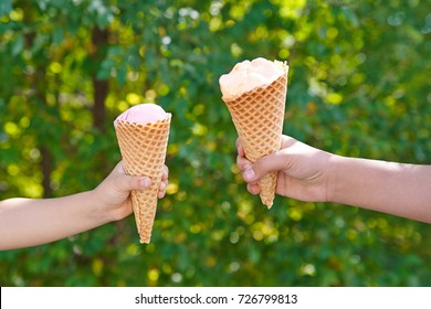 children's hands hold two waffle cones with ice cream on a natural green foliage background