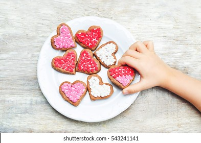 Children's hands holding cookie in the forms of heart. toning. selective focus