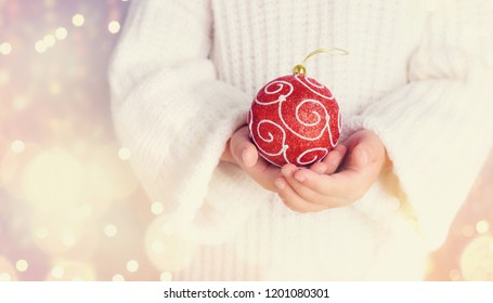 Children's hands holding a red Christmas decoration isolated on shiny background