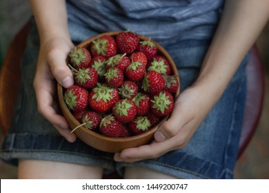 children's hands holding a wooden bowl it is strawberry