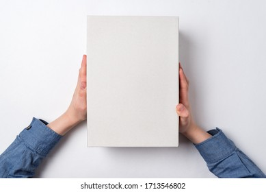 Children's hands holds white cardboard box on white background. Top view. Shipping concept