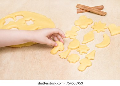 Children's hands make christmas cookies. Children's hands holding cookies of raw dough for christmas