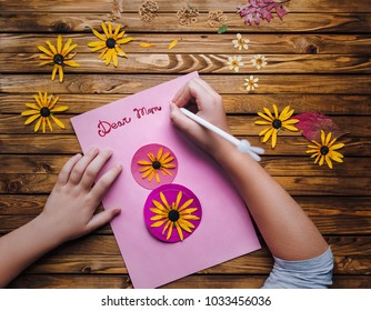 Children's hands make a postcard to her mother in honor of the holiday on the 8th of March. Child creativity, handmade. Dear Mom. Ikebana.