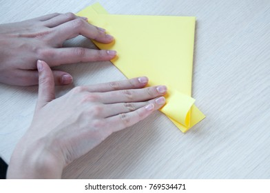 Children's hands make of a yellow paper boat