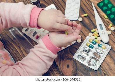 Children's hands with medicines on a wooden table. A small child left unattended plays dangerous drugs.