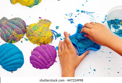 Children's hands molded from colored sand