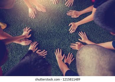 Children's hands on green artificial turf. Kid soccer training  football.