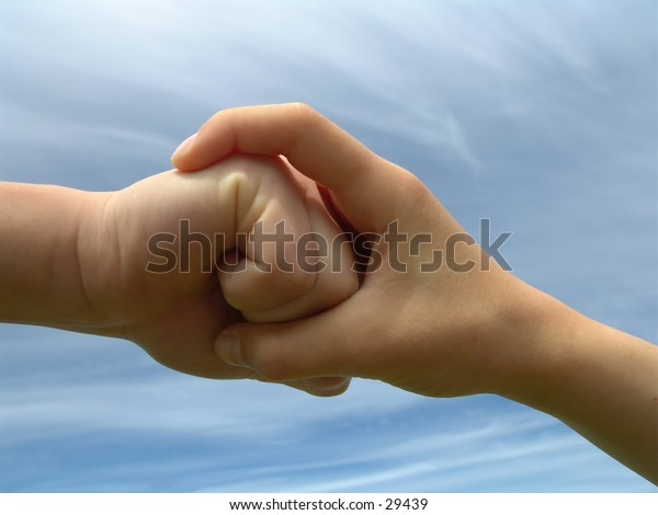 Childrens hands: One hand wrapped around a clutched fist.
