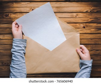 Children's hands open a large brown envelope and take a clean white sheet of paper out of it. Wooden background.