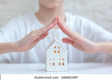 Children's Hands Over House on white background - Home Security And Protection Concept. Stay at home concept.
