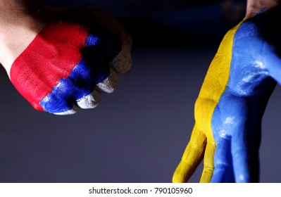 Children's hands are painted color of a flag of Ukraine and Russia