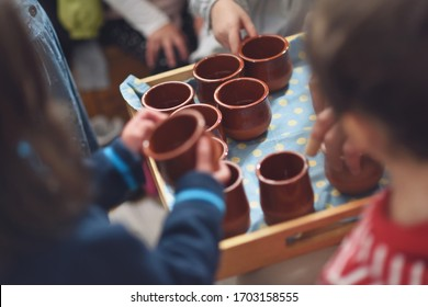 Children's hands picking up earthenware bowls with water in the Waldorf school cast.