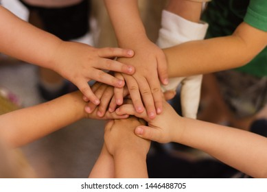 Children's hands piled on top of each other. Children's team and team building among the little guys.