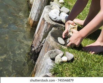 Children's hands play with stones on the water