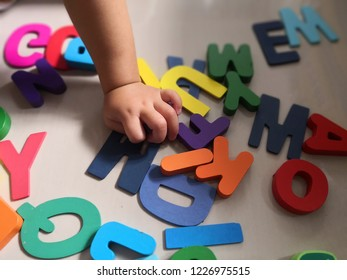 children's hands are playing with abc letters from colorful wood