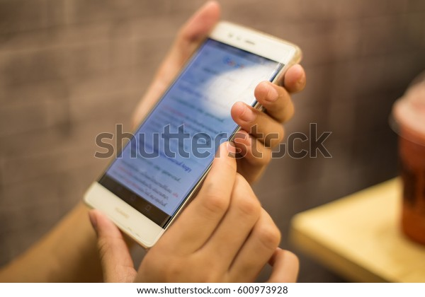 Children's hands playing on phone.