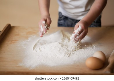 Children's hands pour flour.rolling pin and eggs are on the table The child is played by the chef's chef.